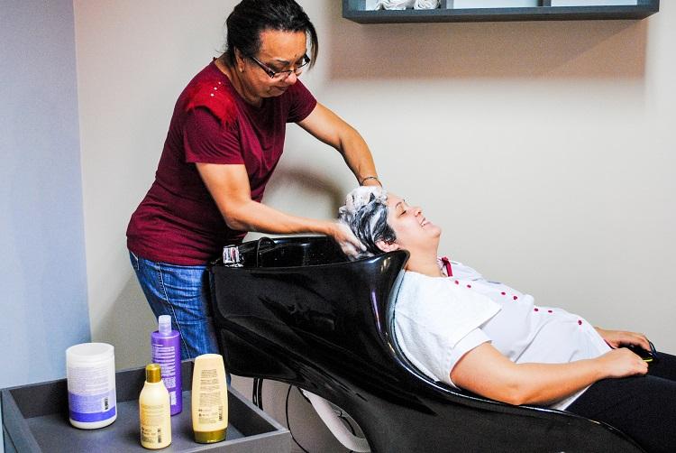 cabeleireira lavando cabelo de mulher em lavatório